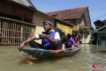 Meski banjir masih terjadi, sejumlah warga tetap bertahan di rumah sehingga untuk beraktivitas menggunakan perahu, Dayeuhkolot, Kabupaten Bandung, Kamis (25/12/2014). Warga enggan meninggalkan rumah demi menjaga dari hal-hal yang tidak diinginkan seperti pencurian. FOTO : FRINO BARIARCIANUR